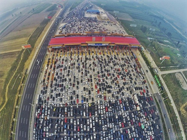 Vehicles are seen stuck in a traffic jam near a toll station as people return home at the end of a week-long national day holiday, in Beijing, China, October 6, 2015. Picture taken October 6, 2015. REUTERS/China Daily CHINA OUT. NO COMMERCIAL OR EDITORIAL SALES IN CHINA - RTS3HL3
